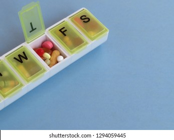 A plastic, daily pill sorter filled with tablets and capsules.  The Thursday pocket is open.  Copy space.