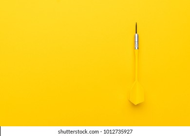 plastic dart with metal tip on the yellow background