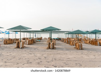 A lot of plastic deckchairs and umbrellas at the sea beach at sunrise. Summer vacation concept.