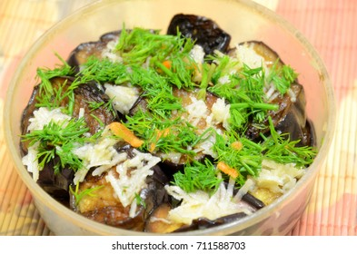 A plastic dish with pickled cut aubergines and spices.