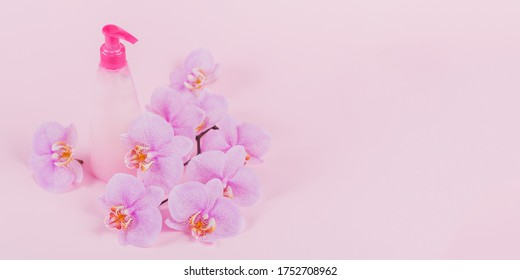Plastic dispenser bottle with liquide cosmetic soap, intimate wash or shower gel, purple sponge and pink orchid flowers on light pink background. Spa and women's hygiene concept