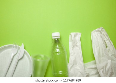 Plastic disposable utensils on green background. fork, knives, plates, cups and a package, bottle,  bag