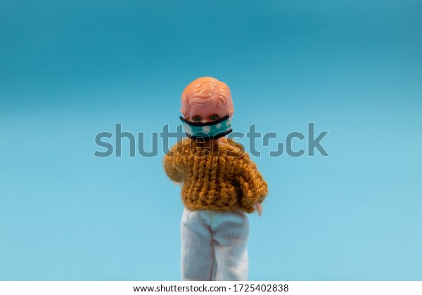 Plastic doll wearing a face mask against a blue background. Room for copy.