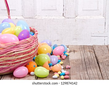 Plastic Easter Eggs With Candy In A Basket On Wooden Background