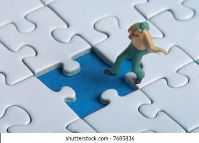 plastic figure falls into a puzzle hole