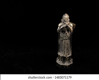 Plastic figure of a knight in armor. Figurine Medieval warrior with a sword and shield, on a black background. Chess piece in silver color.