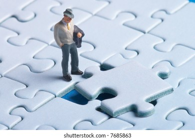 plastic figure standing in front of a puzzle piece