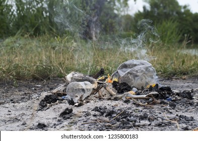 Plastic fire. Environmental pollution: after picnic a fire with a flame burns plastic (plastic containers, bottles and glasses) producing dioxin and toxic air (the smoke of this photo is real)