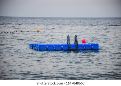 Plastic floating pier in the sea. An anchored raft-like platform, often referred to as a pontoon.