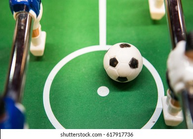 plastic football in the center of soccer field board game surrounding with player figure, selective focus