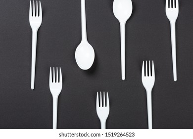 Plastic forks and spoons on gray background