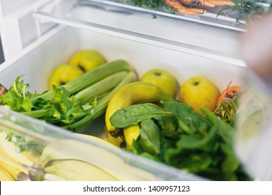 Plastic free bananas,salad, spinach, celery, apples, orange in fridge. Zero waste grocery shopping. Fresh vegetables in opened drawer in refrigerator. Vegetarian diet. Food delivery