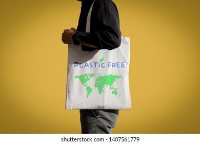 Plastic free save earth concept.Man holding eco bag on yellow background