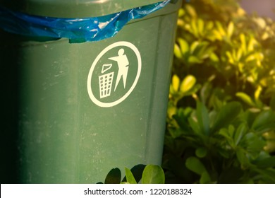 Plastic garbage bin with white symbol on it. Green container box for waste with foliage in background. Public responsibility for clean environment.