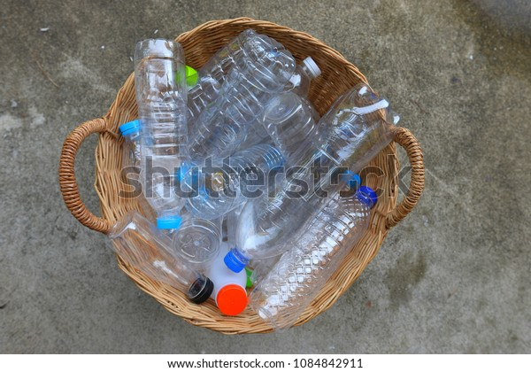 Plastic garbage bottles in brown bamboo basket  on cement floor recycle concept, top view