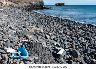 plastic garbage washed up at natural pebble beach