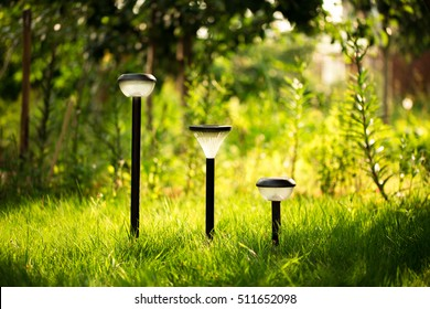 Plastic garden flashlight standing on the ground in the garden green grass. It is shining yellow light. Summer mood image.