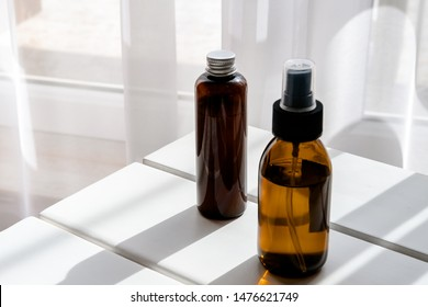 Plastic and glass brown bottles with organic cosmetics on white table. Direct light. Beauty blogging minimalism concept