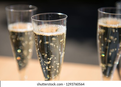 Plastic glass of champagne with sparkling bubbles and two other glasses in background