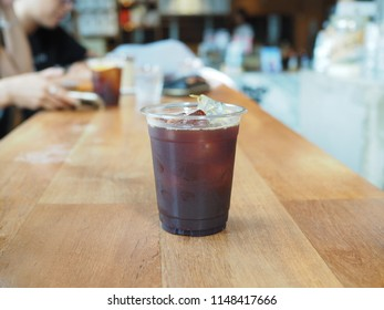 A plastic glass of cold brew coffee added lemon juice, pomegranate juice, orange juice, blueberry syrup decorated with citrus jelly. Selective focus.