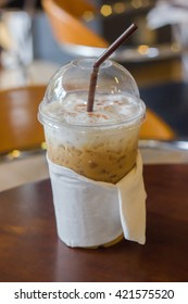 plastic glass of ice coffee on table in cafe shop