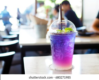 Plastic glass of iced butterfly pea tea with lemon on wooden table. Relax with Thai herbal drink for healthy life in natural concept. Selective focus.