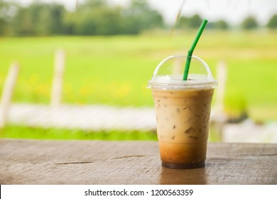 plastic glass of iced coffee on wooden balcony with green nature background