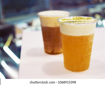 A plastic glass of iced oolong tea (also called wulong or wu long) with layer of cream cheese foam decorated with green tea powder on top, Traditional Chinese Beverage. Selective focus.