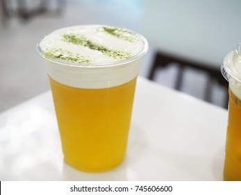 A plastic glass of iced oolong tea (also called wulong or wu long) with layer of cream cheese foam, Traditional Chinese Beverage. Selective focus.