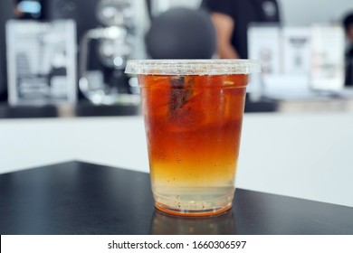 A plastic glass of iced shaken coffee mixed with fruit juice. Lifestyle concept with selective focus.