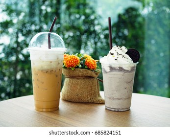 Plastic glasses of iced coffee latte topped with streamed milk and coffee powder and Chocolate frappe topped with whipped cream and cookies decorated with flower bag on wooden table. Selective focus.