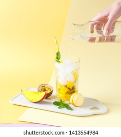 Plastic glasses with lemonade on a colored background, sunlight, fruit and berries. The lemonade to take on the road. Pink and yellow background.