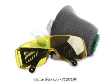 Plastic goggles and respirator on white background