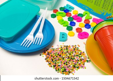 Plastic granules disposable tableware and children's toys made of polyethylene, polypropylene, pet polymer material on a white background. BPA FREE