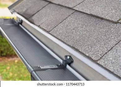 Plastic guard mesh over new dark grey plastic rain gutter on asphalt shingles roof at shallow depth of field.