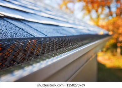 Plastic guard over gutter on a roof, shallow focus on mesh