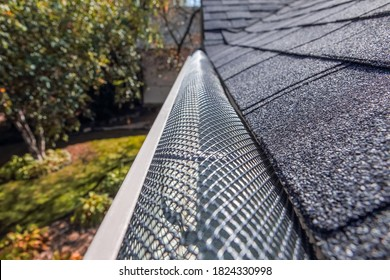 Plastic guard over gutter on a roof to keep it free of leaves, focus in center