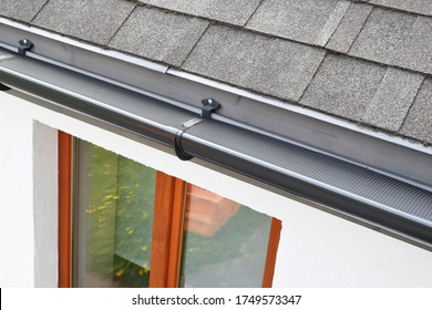 Plastic guard over new dark grey plastic rain gutter on asphalt shingles roof and white color decorative plaster facade with brown wooden window with reflection on glass pane.