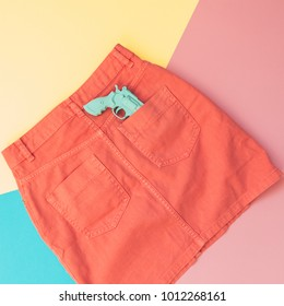 plastic gun in the pocket of the orange denim skirt. pastel minimal. fashion woman clothes