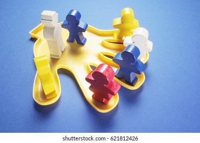 Plastic Hand with Wooden Figures on Blue Background