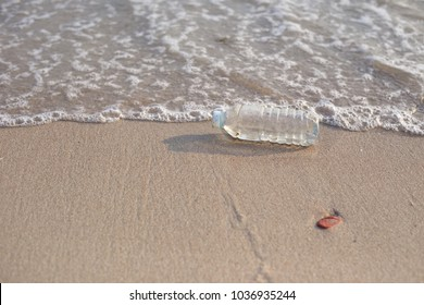 plastic jars are dumped at the beach. Is the toxic mass at the environment.