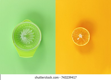 Plastic juicer and fresh orange, isolated on green and orange pastel color background