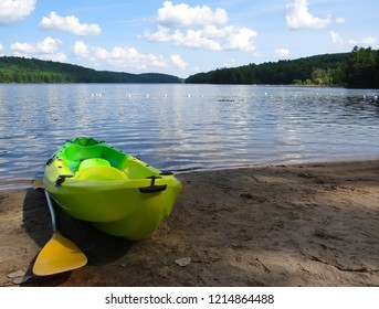 Plastic kayak and a paddle on sandy beach of the lake with white clouds  reflected in calm water. Philippe Lake. Gatineau Park Quebec