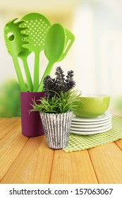 Plastic kitchen utensils in stand with clean dishes on table on bright background