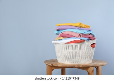 Plastic laundry basket with clean clothes on stool against color background. Space for text