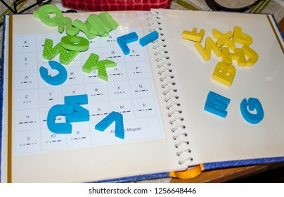 the plastic letters of the alphabet lying on the opened book Russian Cyrillics.