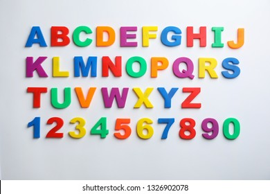 Plastic magnetic letters and numbers isolated on white, top view