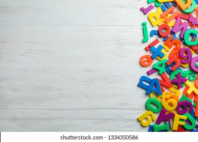 Plastic magnetic letters on wooden background, top view with space for text