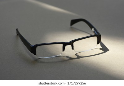 a plastic man eyeglasses with its shadow