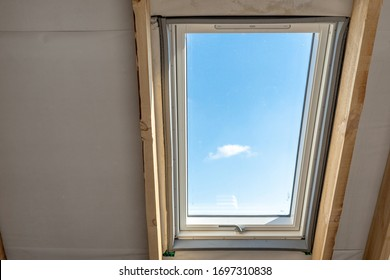 Plastic mansard window with triple glasses and view on clear blue sky at roof, in new house under construction with copy space wall